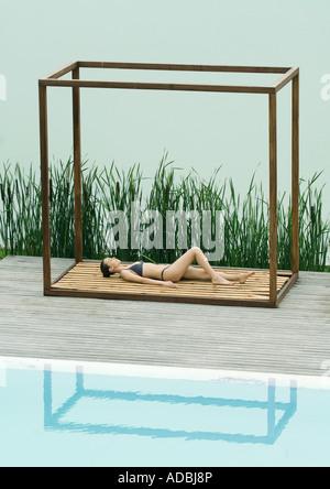 Woman wearing bikini, allongé sur le dos dans la structure carrée entre le lac et la piscine Banque D'Images