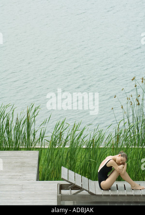 Femme assise sur une chaise longue à côté du lac, serrant les genoux, la tête reposant sur les armes Banque D'Images