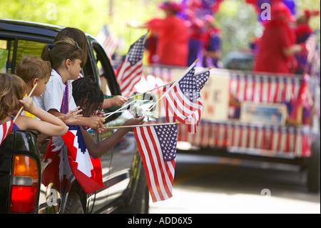 Les enfants de courses multi brandissant des drapeaux à l'arrière d'une camionnette pendant un défilé du 4 juillet Banque D'Images