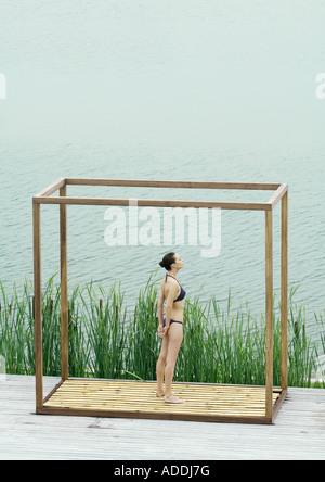 Jeune femme debout à l'intérieur de structure carrée, à côté de plan d'eau Banque D'Images