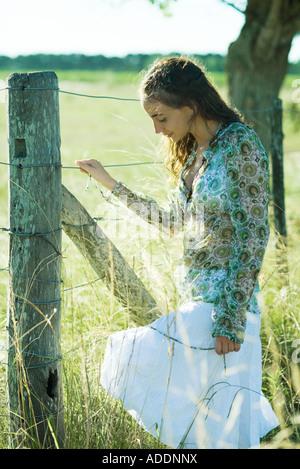 Jeune femme debout à côté d'une clôture rurale, regardant vers le bas
