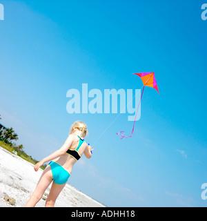 Enfant sur beach red kite flying in sky Banque D'Images