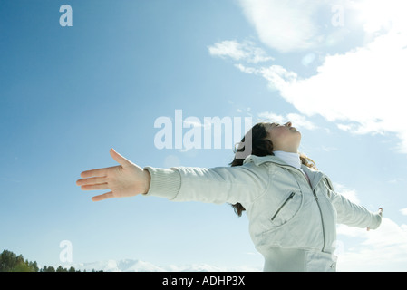 Teen Girl standing in snowy landscape, bras levés de soleil Banque D'Images