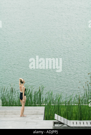 Woman in swimsuit standing sur le pont, en regardant vers l'eau Banque D'Images