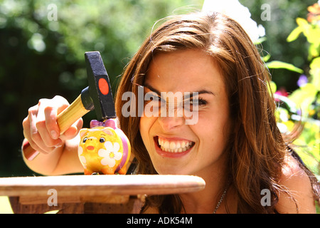 Jeune femme vole une tirelire avec un marteau © Peter Schatz/Alamy Banque D'Images