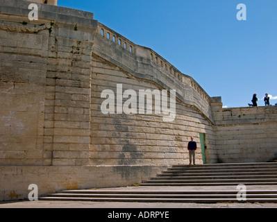 Un homme dans la distance se trouve au sommet de certaines marches de pierre en face d'un vieux mur avec balustrades Banque D'Images