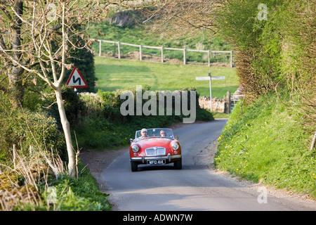 Voiture de sport MG décapotable voyageant sur la route de campagne sinueuse Swinbrook Oxfordshire les Cotswolds Banque D'Images