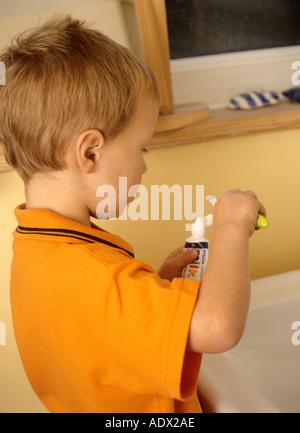 Jeune garçon se brosser les dents avec du dentifrice Banque D'Images