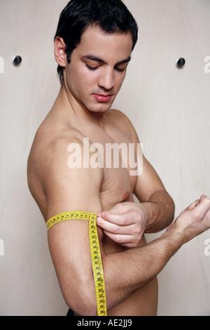 L'homme la mesure de son muscle du bras Banque D'Images