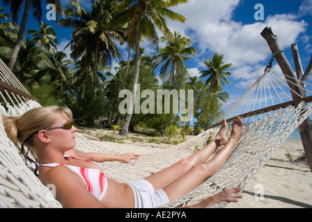 Girl in hammock on tropical beach à Aitutaki, aux Îles Cook dans le Pacifique Sud Banque D'Images