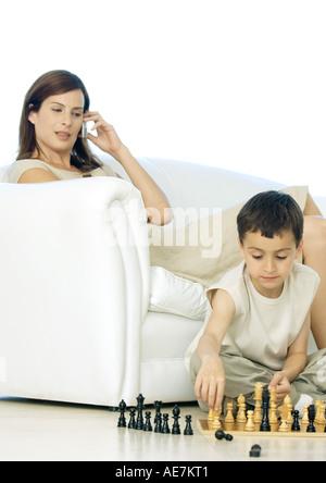 Garçon jouant avec jeu d'alors que mère utilise le téléphone cellulaire Banque D'Images
