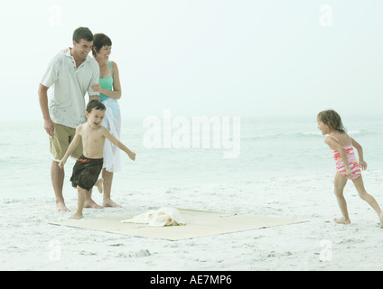 Famille à la plage, les enfants courir autour de tapis de plage