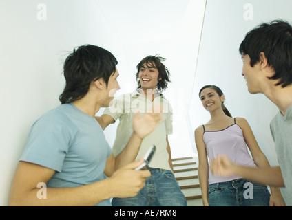 Quatre jeunes amis réunion en escalier Banque D'Images