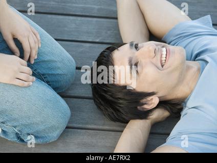 Jeune homme couchée sur le sol avec les mains derrière la tête, souriant, quelqu'un s'agenouiller à côté de lui, vue partielle