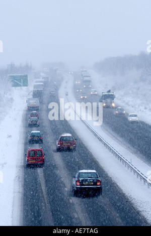 Les voitures et les camions roulant sur deux carrageway en hiver la neige.
