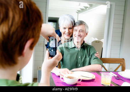 Boy taking picture of senior couple with camera phone Banque D'Images
