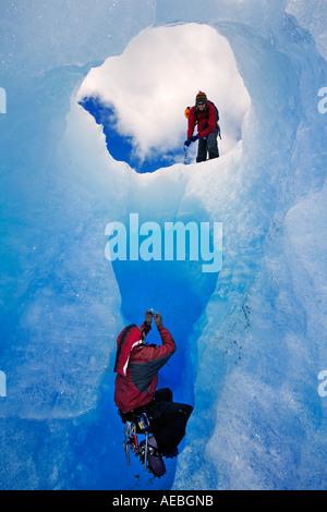 Deux alpinistes en photographiant la grotte de glace de l'autre. Gris Glacier Parc National Torres del Paine au Banque D'Images