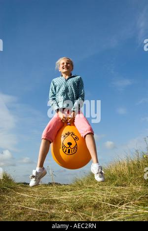 Jeune fille de rebondir sur un Space Hopper, England UK Banque D'Images