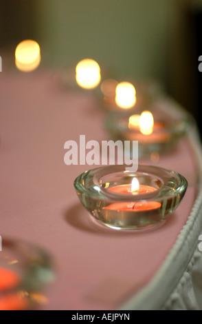Bougies chauffe-plat rose sur le bord d'une table ronde. Banque D'Images