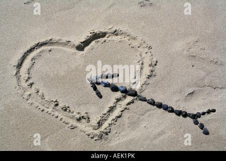 Un coeur dans le sable avec une flèche faite de pierres Banque D'Images