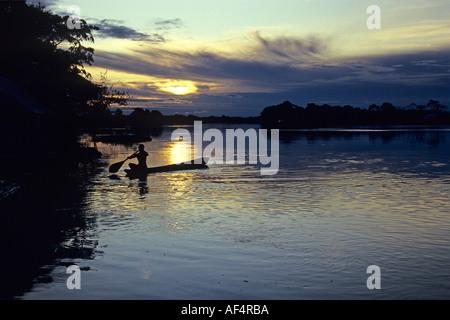 Pagaies canoe homme local contre le coucher du soleil sur la rivière et la silhouette du paysage de forêt tropicale Banque D'Images