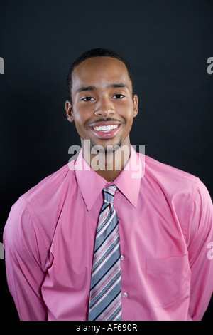 Portrait of a young smiling 18 ans African American man portant une chemise et cravate rayée rose Banque D'Images