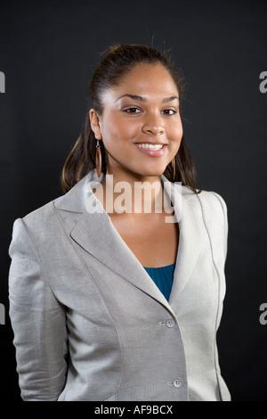 Portrait of a young smiling 18 ans African American Woman wearing costume gris argent ou un manteau et avec les Banque D'Images