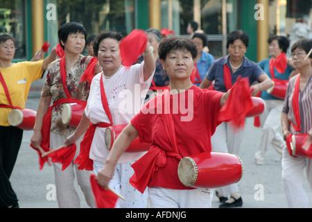 Les femmes avec batterie faire la gymnastique à l'extérieur tôt le matin de la ville de Yinchuan Ningxia Chine Août Banque D'Images