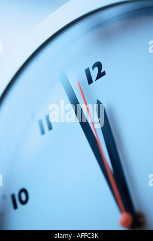 Gros plan d'une seconde main rouge près de minuit sur une horloge murale Banque D'Images