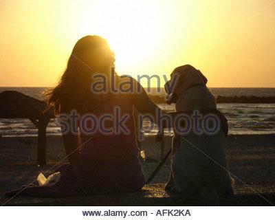 Silhouette of young woman hugging her dog au littoral méditerranéen de Tel Aviv en Israël Banque D'Images
