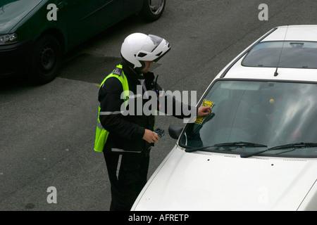 Directeur de trafic ou préposé au stationnement qui émet un billet à une voiture garée dans un quartier résidentiel Banque D'Images