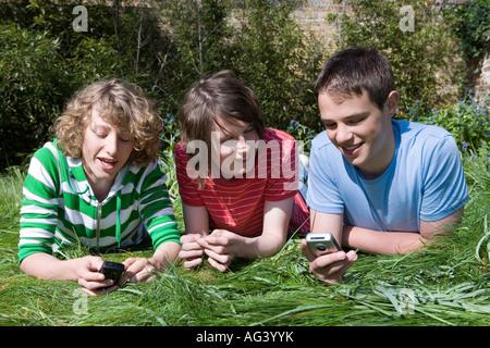 Des amis à l'aide de leur téléphone cellulaire Banque D'Images