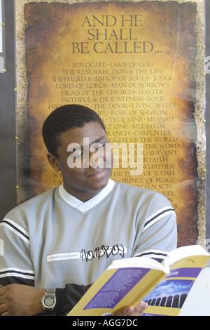 Homme Black Student au travail étudiant à partir du texte du livre en face de l'affiche de la religieuse Banque D'Images