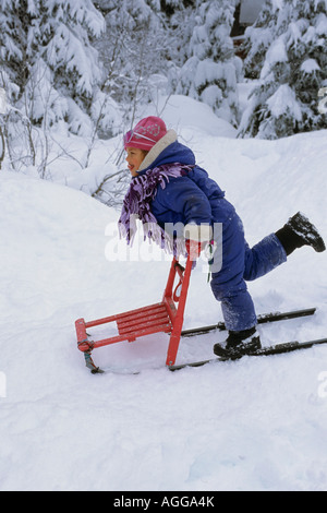 Jeune fille jouant sur la trottinette des neiges dans la neige profonde SC AK Winter Banque D'Images