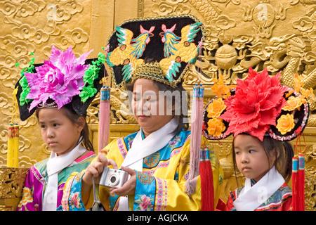 Asie Chine mère avec deux enfants dans les vêtements traditionnels photographiée Banque D'Images