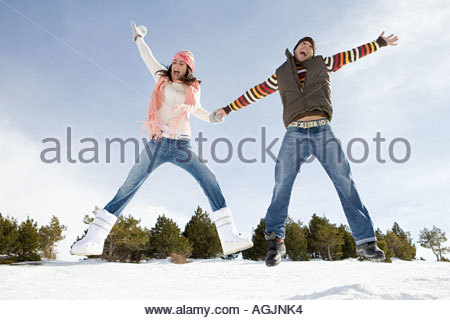 Couple jumping in snow Banque D'Images