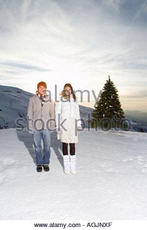 Couple debout près d'un arbre de Noël à la montagne Banque D'Images