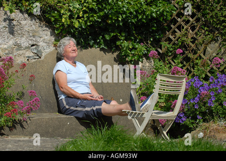 Un retraité femme bénéficie d'un bain de soleil dans son jardin à l'AUTOMNE LA RETRAITE RE ANS.UK Banque D'Images