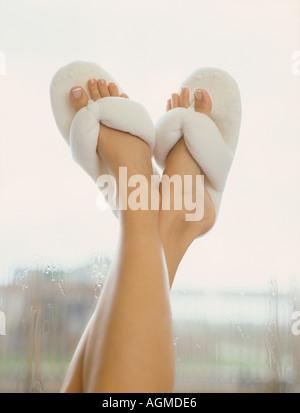 Jeune femme en éponge, pantoufles avec pieds sur la fenêtre Banque D'Images