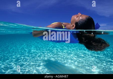 Banc de Grand Cayman en vertu d'une femme flottant dans l'eau claire Banque D'Images