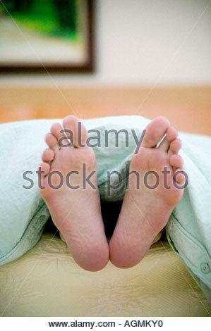 Une paire de dames qui sort d pieds sous les couvertures sur le lit Banque D'Images