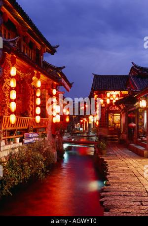 Rue Pavée, et des cours d'eau au crépuscule Lijiang Yunnan Province Chine Banque D'Images