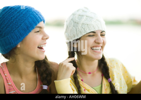 Young female friends wearing knit hats, rire Banque D'Images