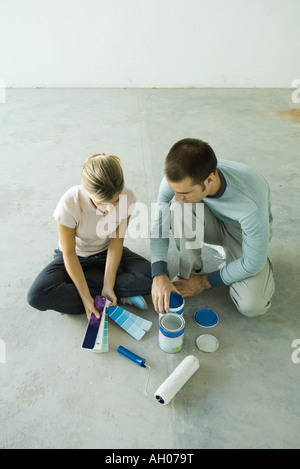 Couple sitting on floor looking at color swatches Banque D'Images