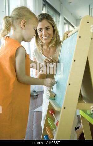 Femme regardant petite fille dessiner on chalkboard Banque D'Images