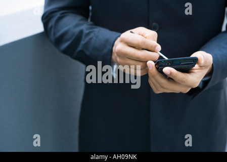 Businessman using palmtop, cropped view of hands