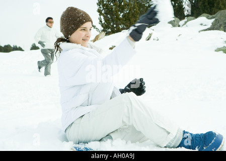 Teenage girl sitting on ground in snow, lancer snowball, side view Banque D'Images