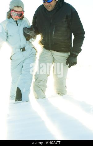 Père et fille dans la neige marcher ensemble, se tenir la main, cropped view Banque D'Images