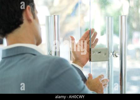 L'homme l'inspection verrou sur porte en verre Banque D'Images