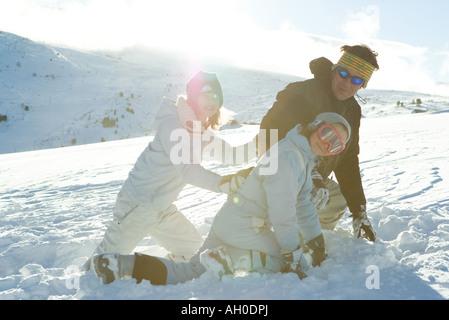 Son père et ses deux filles crouching in snow, smiling Banque D'Images